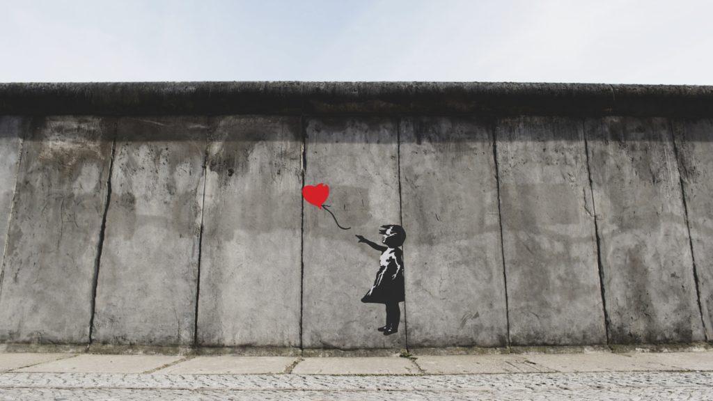 赤い風船に手を伸ばす少女