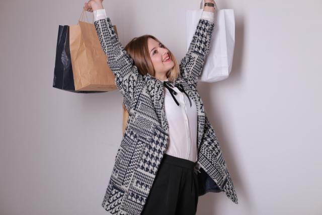 紙袋を大量に抱える女性